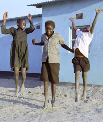 tn_three_children_jumping_in_front_of_house